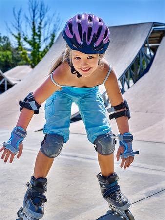 niño en patines: Diversión chica de deportes activos montar en patines en el parque de patinaje.