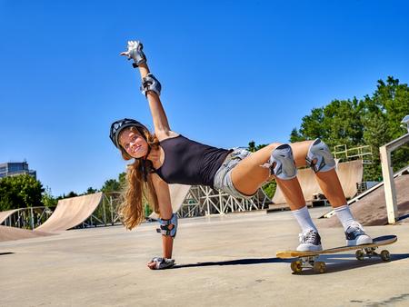stunt: Teen girl rides his skateboard outdoor. Girl do  stunt aganist blue sky. Summer sports.