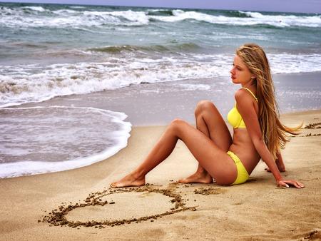 ragazze bionde: mare ragazza di estate. Adolescente dissipa il cuore gamba sulla sabbia. Archivio Fotografico