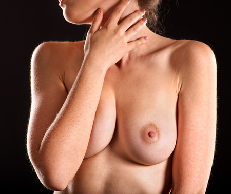 naked woman: Girl with beautiful nude topless breasts coverds herself on black background. Womens Health. Stock Photo