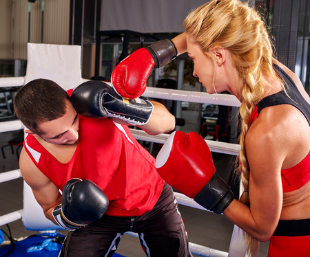combative sport: Female boxer with your male coach on workout in gym. Girl shoots  man in ear.