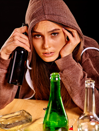 dipsomania: Drunk girl holding green glass bottle of alcohol. Soccial issue alcoholism.