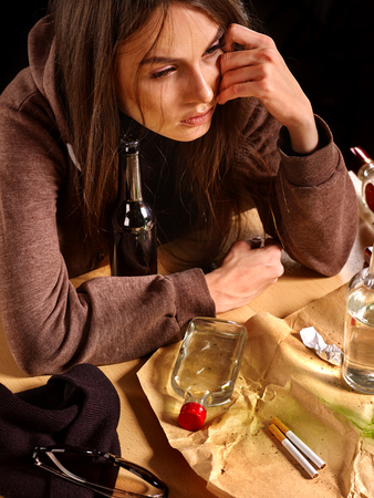 dipsomania: Drunk girl girl sitting, his head in his hand with bottle of alcohol. Soccial issue alcoholism.