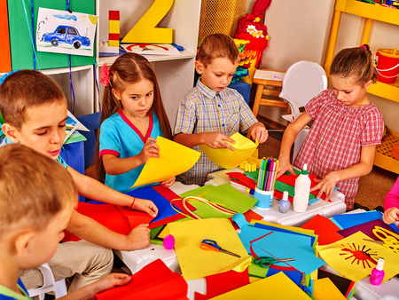kindergartener: Group kids keeps colored paper and glue on table in kindergarten . Stock Photo