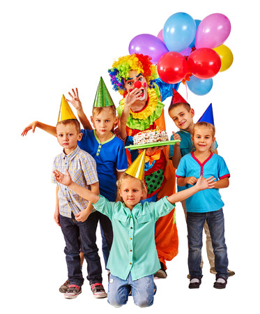 child birthday: Clown keeps bunch of balloons and birthday cake with group children posing at camera. Isolated. Stock Photo