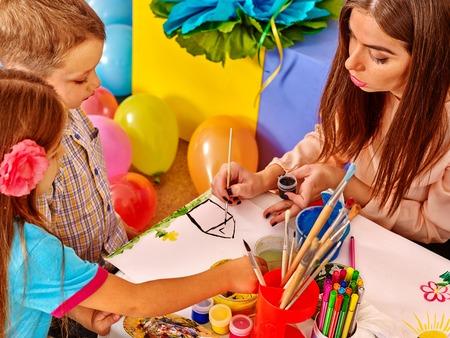 maestra preescolar: Los niños con la mujer del profesor de pintura sobre papel a la mesa en el jardín de infantes. Globos en el piso.