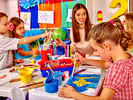 painting art: Children with teacher woman painting on paper and communicate with each other at table  in  kindergarten .