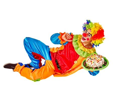 full height: Happy birthday clown holding cake and lying on the floor.  Isolated.