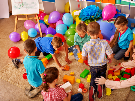 Group children game blocks on floor in kindergarten . Balloons on floor Top view. Stockfoto