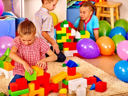 early education: Group children game blocks  in kindergarten . Balloons on floor. Top view. Stock Photo