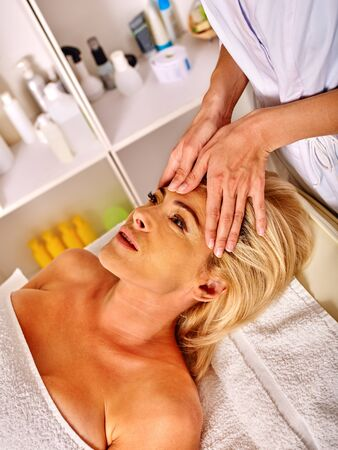 rejuvenating: Woman middle-aged take face and neck rejuvenating massage in spa salon.
