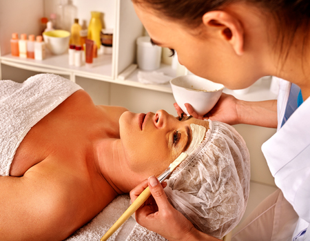 rejuvenating: Woman middle-aged gets rejuvenating facial and neck clay mask in spa salon. Two female people.
