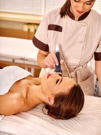 rejuvenating: Young woman gets rejuvenating electric ultrusound facial massage at beauty salon.