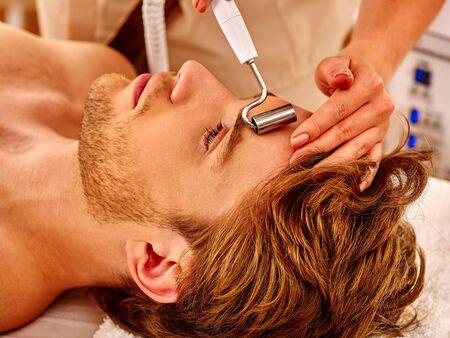 sound therapist: Man gets rejuvenating electric galvanic face spa massage at beauty salon. Stock Photo