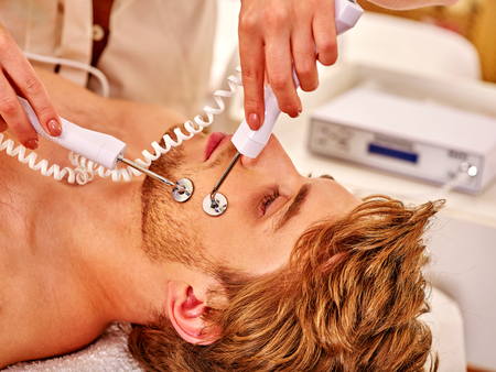 sound therapist: Man gets revitalizing electric facial peeling hydradermie at beauty salon.