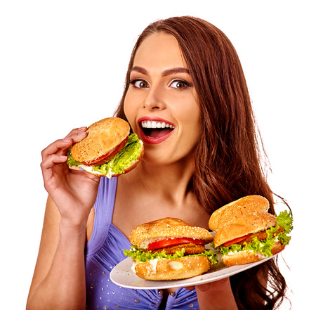 fastfood: Girl holding and eating several hamburgers. Fastfood concept .