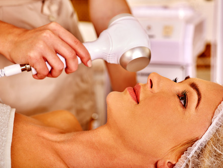 ultrasonic: Close up of young woman in hat gets revitalizing electric ultrasonic facial massage at beauty salon. Stock Photo