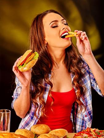 fastfood: Cô gái ăn với hương vị thức ăn nhanh bánh hamburger lớn và khoai tây chiên.