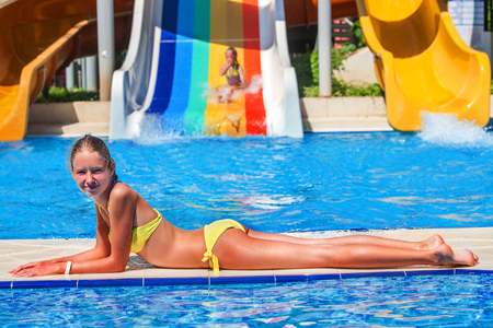water   slide: girl lying on the side of the pool. Second child riding a water slide. Stock Photo