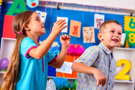 niÑos en el colegio: niños que juegan con grupo de aviones de origami en la guardería. Chica mirando hacia arriba. El niño es feliz.