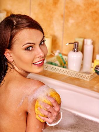 relaxion: Young woman take bubble  bath. Woman washing her shoulder. She is happy.