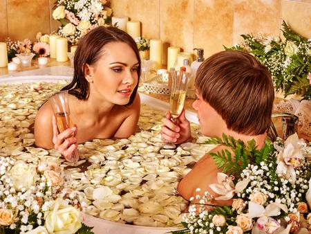 vasos de agua: Pares cariñosos con las copas de champán se relaja en el baño con pétalos de flores. SPA-centro Foto de archivo