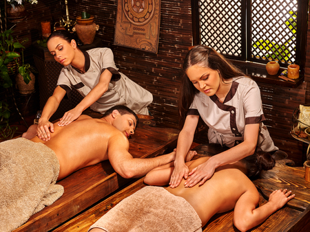soothing: Loving couple  with a soothing ayurvedic spa treatment  in front of a wooden window. Oil massage in  Spa salon. Spa salon decoreted bamboo.
