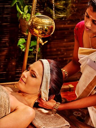 window treatments: Woman with Shirodhara make pouring oil on the head of a spa in India. Preparatory procedures.