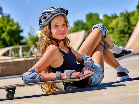 board shorts: Teen girl in helmet sitting on his skateboard outdoor. Fall on person . Girl lying on a skateboard in a skate park.