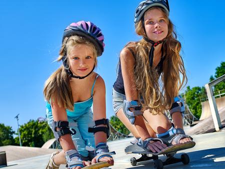 season photos: Two Children in helmet skateboarding on his skateboard outdoor. lower plan. Very happy.