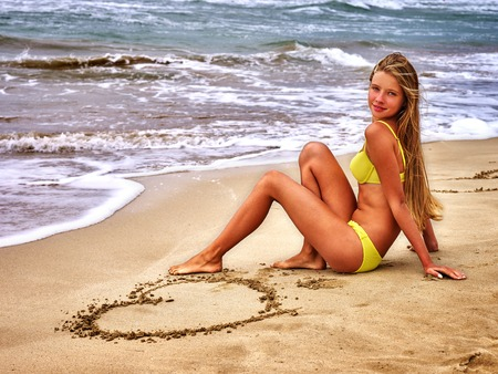 Girl sitting on the beach draw a heart in the sand. Romantic Summer.