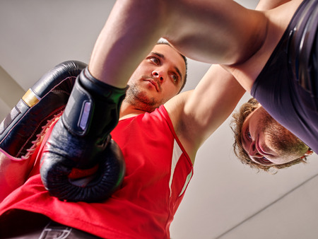 handsome young man: Two  men boxer wearing  gloves boxing . They are serious. Stock Photo
