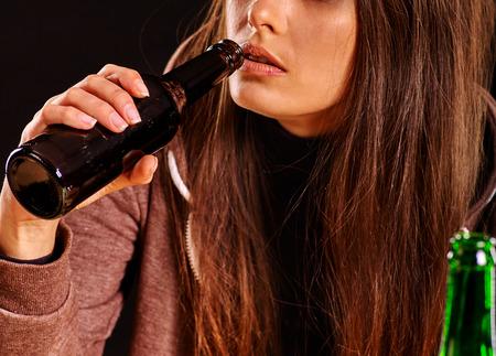 dipsomania: Drunk girl holding bottle of alcohol. Home alcoholism.