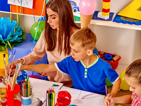 kids club: Happy children and teacher draw paints in the kids club. Stock Photo