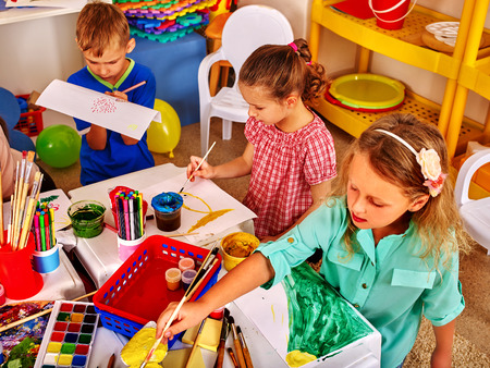 kids club: Group of children having fun painting beautiful pictures of the kids club. Stock Photo