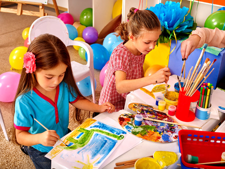 kindergarden: Two girls paint colors. Balloons in the background. Stock Photo
