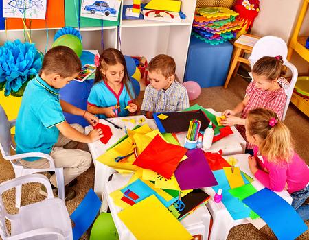 Gruppe Kinder im Kindergarten farbigem Papier auf dem Tisch zu halten. Kinder verwenden, um einen farbigen Origami-Papier.
