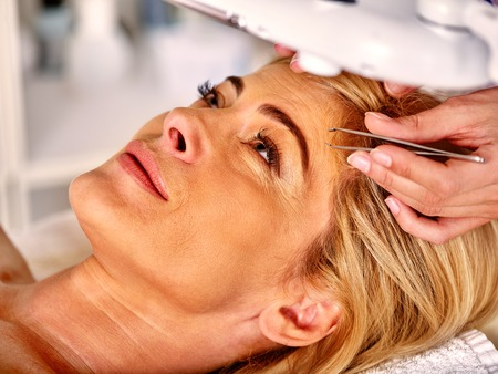 tweezing eyebrow: Woman middle-aged in spa salon with young beautician. Tweezing eyebrow by beautician. Woman in a retracting eyebrows spa.