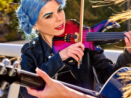 lonesomeness: Music street performers girl with blue hair violinist  playing  aganist sky with clouds outdoor. The second girl - violinist with her. Stock Photo