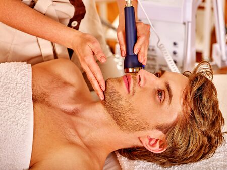 electrophoresis: Relaxed young man luxuriating on electroporation  facial therapy at beauty salon. Stock Photo