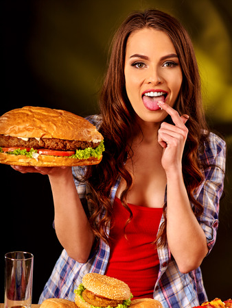 niña comiendo: Niña de comer hamburguesa con dos lados. concepto de la comida rápida. Foto de archivo