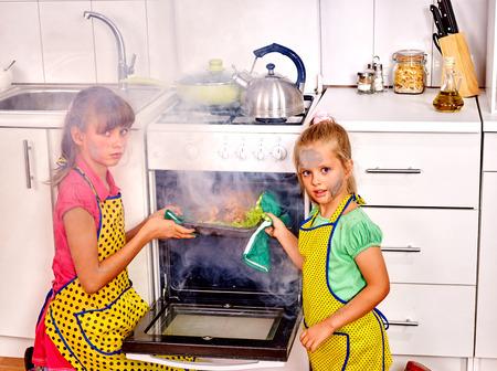 quemado: Los niños con un pollo de cocina quemado en la cocina. Fumar. Las caras de los niños manchados de hollín.