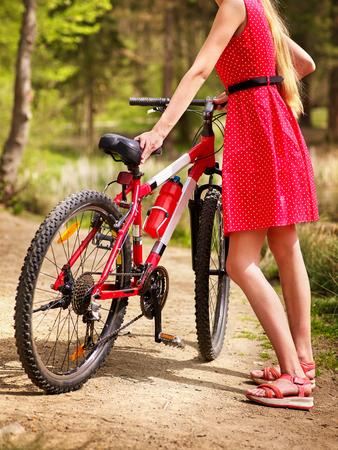 lunares rojos: Bicicletas Ciclo de la muchacha. Niñas el uso de lunares rojos visten paseos en bicicleta en el parque. Chica en el ecoturismo. El ciclismo es bueno para la salud. Ciclista es irreconocible. Foto de archivo