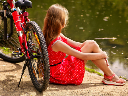 lunares rojos: Bicicletas Ciclo de la muchacha. Niñas el uso de lunares rojos visten paseos en bicicleta en el parque. Chica en el ecoturismo. La muchacha se sienta apoyado en una bicicleta en la orilla Foto de archivo