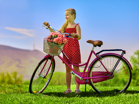 red polka dots: Bicicletas Ciclo de la muchacha. La muchacha del niño que lleva lunares rojos vestido de paseos en bicicleta con flores canasta. Las montañas y el cielo azul en el fondo.