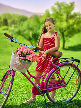 lunares rojos: Bicicletas chica bicicleta. La muchacha del niño que lleva lunares rojos vestido de descanso cerca de la bicicleta con flores canasta. Lote de árbol verde y el cielo azul en el fondo. Foto de archivo
