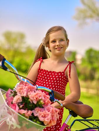 lunares rojos: Bicicletas chica bicicleta. Retrato de ni�a de ni�o con lunares rojos vestido de la bicicleta resto kepps con flores canasta. Parque al aire libre.