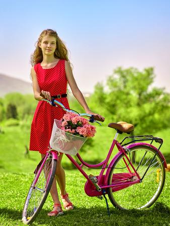 lunares rojos: Bicicletas chica bicicleta. chica adolescente con lunares rojos alineada que mira la cámara mantiene la bicicleta con flores canasta. Lote de árbol verde y el cielo azul en el parque.