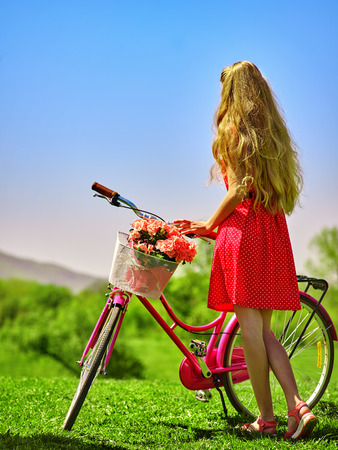red polka dots: Bicicletas chica bicicleta. chica adolescente con lunares rojos alineada que mira en la distancia mantiene la bicicleta con flores canasta. Césped verde. Vista trasera.
