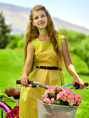 romantic sky: Bikes bicycle girl. Teenager girl wearing yellow polka dots dress looking dreamily keeps bicycle with flowers basket.  Lot of green tree and blu sky in park. Romantic style. Stock Photo